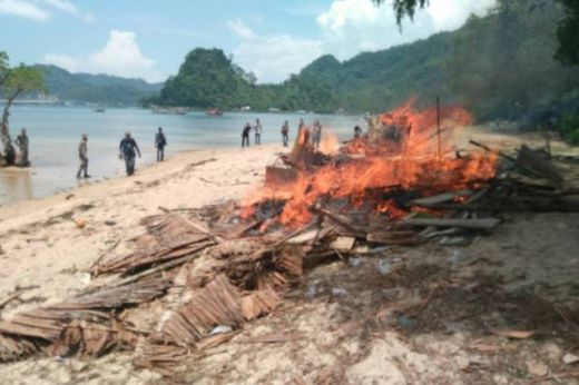 Puing pondok dibakar petugas di tepian pantai. (Humas)