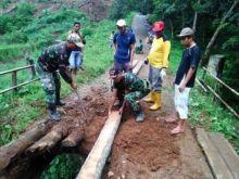 Babinsa dan Warga Bahu Membahu Perbaiki Jembatan Tiumang Dharmasraya