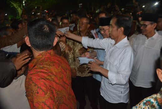 Presiden Jokowi bagikan buku kepada warga.