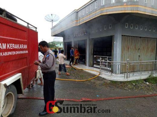 Petugas pemadam kebakaran melakukan pendinginan bangunan.